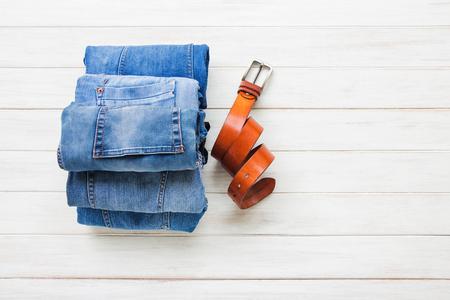 Die zufälligen Ausrüstungen der Männer mit Jeanskleidung und -gurt auf weißem Hintergrund des Hintergrundes, Mode und Schönheitskonzept des hölzernen Brettes, flache Lage Standard-Bild - 87956377