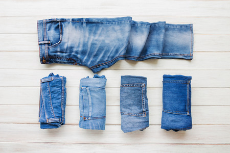 Die zufälligen Ausstattungen der Männer mit Jeans, die auf weißem Hintergrund des hölzernen Brettes, Mode- und Schönheitskonzept, flache Lage kleiden Standard-Bild - 87956378