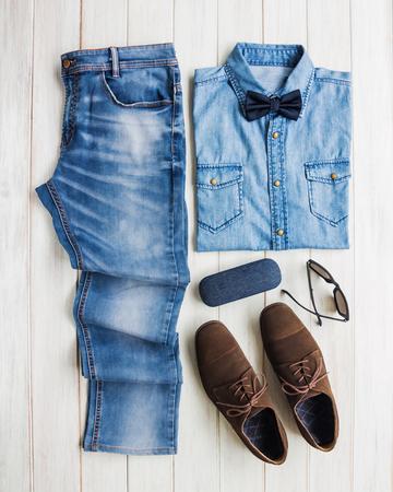 Die zufälligen Ausstattungen der Männer mit Jeans kleiden und Zubehör auf weißem Hintergrund des hölzernen Brettes, Mode und Schönheit, flache Lage Standard-Bild - 87956379