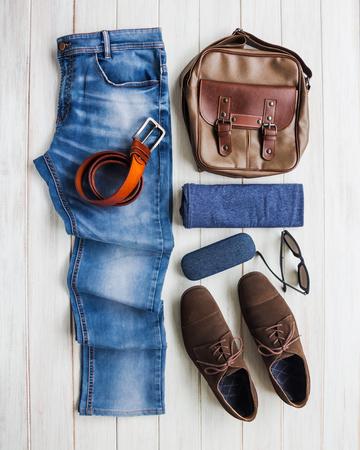 Die zufälligen Ausstattungen der Männer mit Jeans kleiden und Zubehör auf weißem Hintergrund des hölzernen Brettes, Mode und Schönheit, flache Lage Standard-Bild - 87956380
