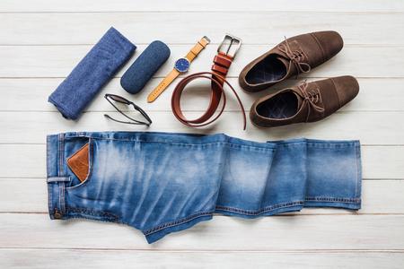 Die zufälligen Ausstattungen der Männer mit Jeans kleiden und Zubehör auf weißem Hintergrund des hölzernen Brettes, Mode und Schönheit, flache Lage Standard-Bild - 87956382