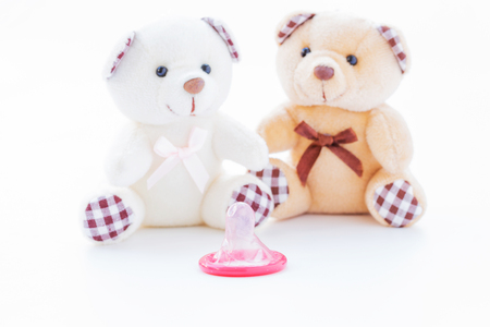Red condom and lovely teddy bear on white background, Valentine day concept Standard-Bild - 94749563