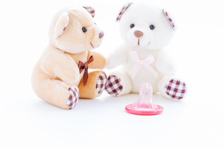Red condom and lovely teddy bear on white background, Valentine day concept Standard-Bild - 94744698
