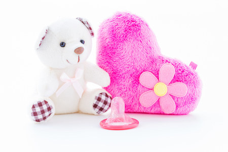 Red condom and lovely teddy bear on white background, Valentine day concept