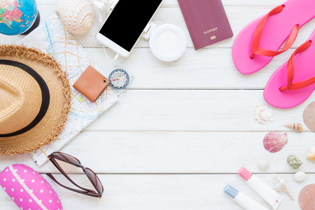 Women's accessories and essential travel items on white wooden board background