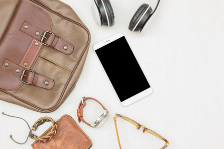 Men's accessories, essential travel items on white rustic wooden background with space