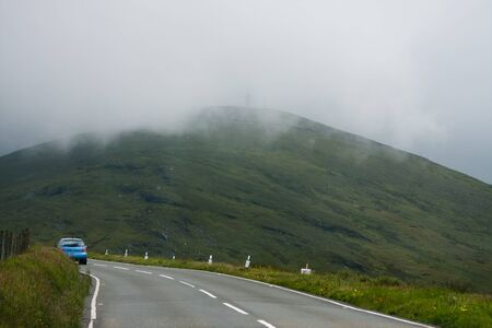 Mountain road in Isle Of Man, with car in front  photo