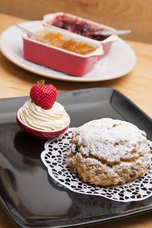 Homemade fruit scone with jam and cream
