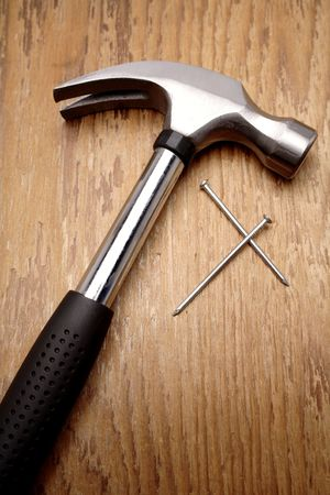 carpenter items: Hammer and nails on wooden panel Stock Photo