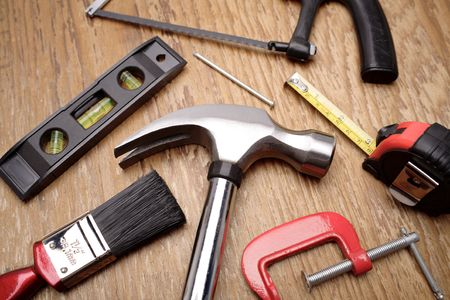 Assorted tools on wooden panel Stock Photo