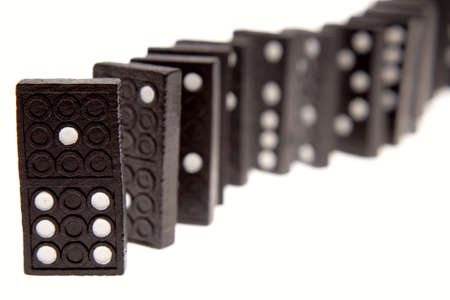 erect: Dominoes standing in a row over white Stock Photo
