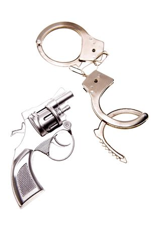Handgun and handcuffs isolated over white background photo