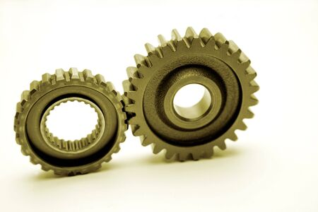 meshing: Two gears meshing together over white
