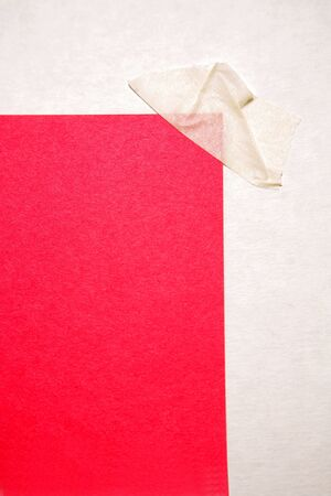 taped: Piece of red paper taped in corner Stock Photo