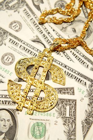 Golden dollar-symbol necklace on cash photo