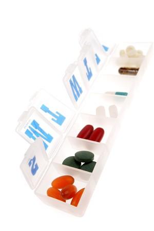 Pills in pillbox on white photo
