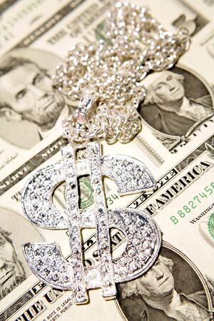 Silver dollar-symbol necklace on money photo