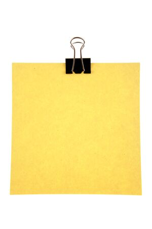 Blank yellow paper held by clip on white background photo