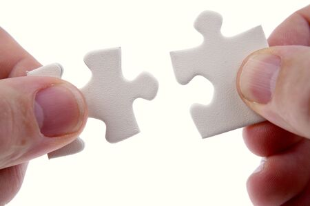 Fingers holding two puzzle pieces Stock Photo - 4638199