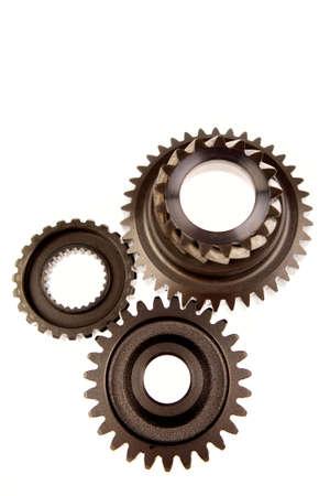 Three steel cogwheels meshing together over white photo