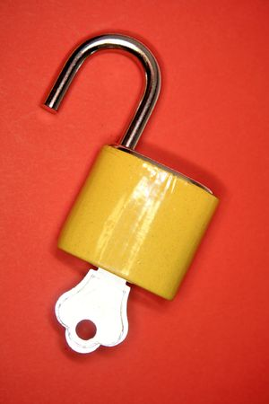 unleash: Open padlock and key on red Stock Photo