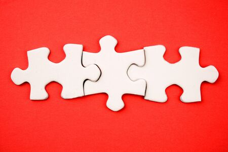 Three jigsaw puzzle pieces on red photo