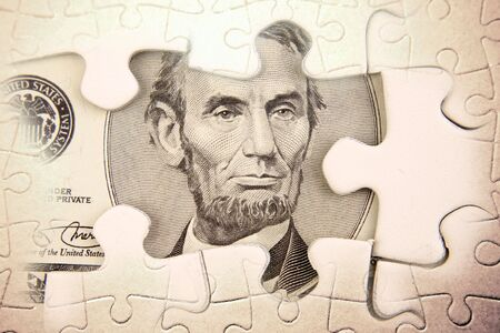 abraham lincoln: U.S. five dollars and puzzle pieces  Stock Photo