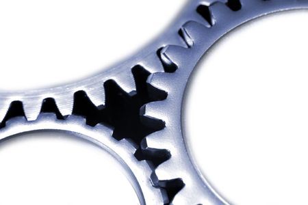 interlink: Close-up of three steel gears on white. Copy space.