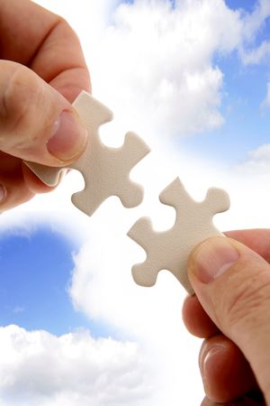 Fingers holding two puzzle pieces in front of blue sky. photo