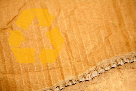 Recycling symbol on ripped cardboard. Copy space. photo
