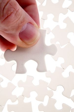 Fingers holding jigsaw puzzle piece    Stock Photo - 5916076