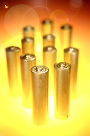 energize: Shiny batteries on abstract color background Stock Photo
