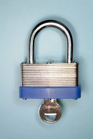 Padlock and key on blue  photo