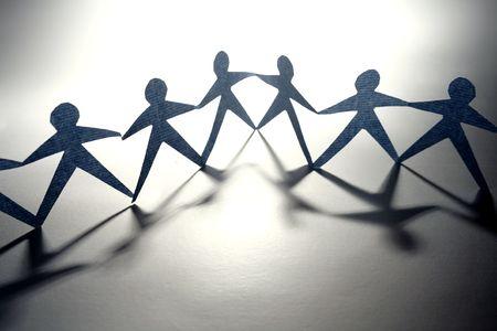 work together: Papier-keten mensen hand in hand in een rij