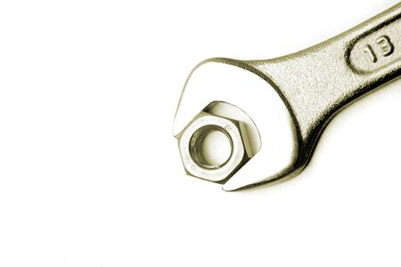 Spanner and nut  on plain background photo