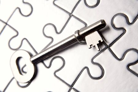 Single key resting on jigsaw puzzle Stock Photo