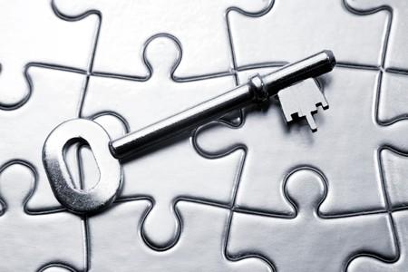 Single key resting on jigsaw puzzle photo