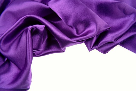 Closeup of purple silk fabric on white background photo