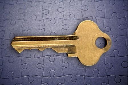 Single key resting on jigsaw puzzle Stock Photo - 7658056