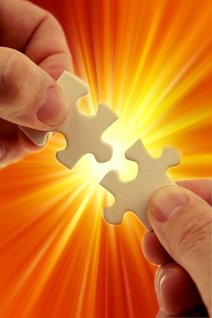 Fingers holding two puzzle pieces over bright background  photo