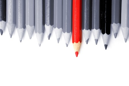 standing out of the crowd: One red pencil standing out from dull pencils Stock Photo