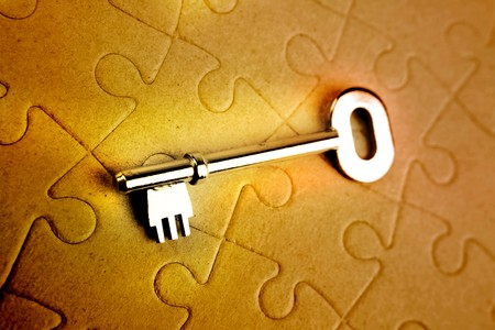 Single key resting on jigsaw puzzle Stock Photo - 7733360