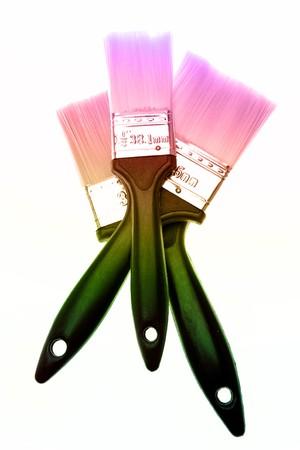 Closeup of three colorful paintbrushes on white photo