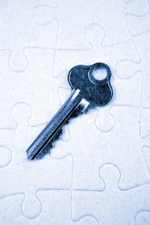 Single key resting on jigsaw puzzle Stock Photo - 7893107