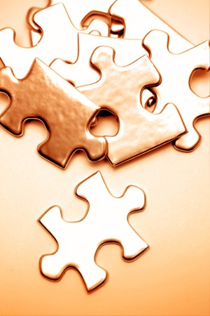 Jigsaw puzzle pieces scattered on brown background  Stock Photo - 7893153