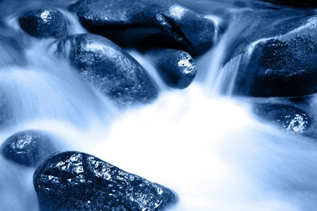 Stream flowing in motion over rocks. Natural background  photo