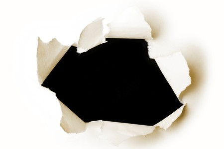 Hole ripped in paper on black Stock Photo - 8127435