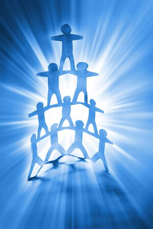 Human team pyramid on bright blue background photo