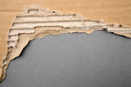 Hole ripped in cardboard on gray background photo