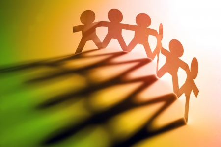 support team: Six people holding hands, casting shadows Stock Photo